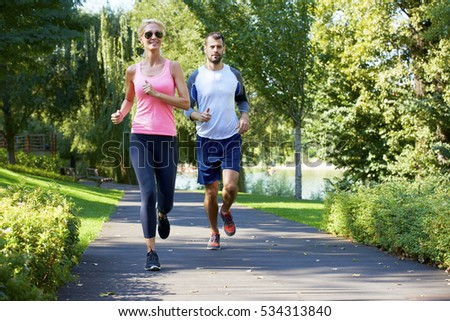 Shot of a young woman and man running outdoor.