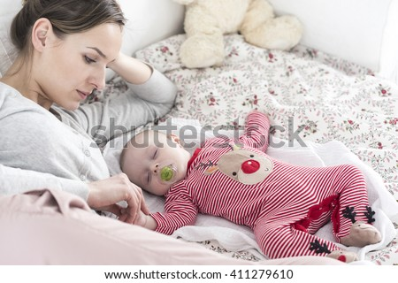 Shot of a young woman looking at her sleeping baby - stock photo