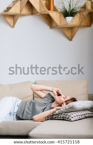 Shot of a young woman lying on sofa and talking on her phone at home