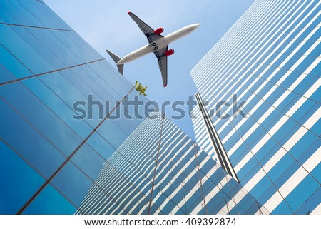 Shot of airplane flying above glass office buildings. - stock photo