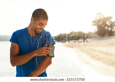 Shot of an attractive and sporty young man starting his music play list outdoors. - stock photo