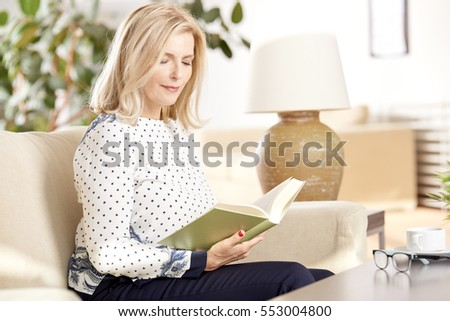 Shot of an attractive blond woman reading a book at home while relaxing.