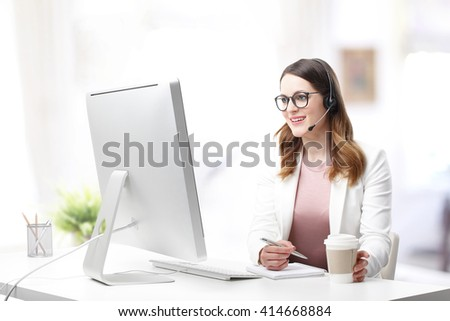 Shot of an attractive customer support agent sitting at her workplace and chatting online. - stock photo