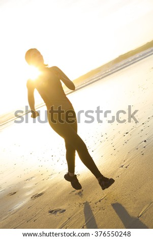 Shot of an attractive young woman running outdoor at the beach - stock photo