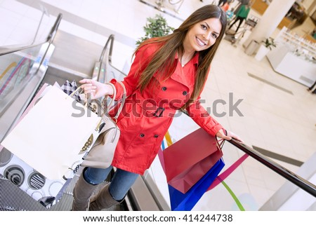 Shot of an attractive young woman shopping.Woman holding paper bags and looking at camera. - stock photo