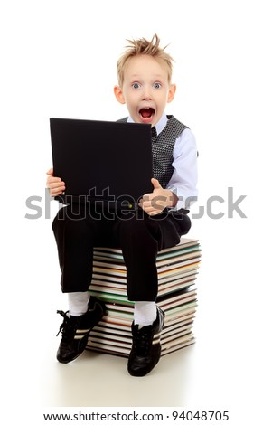 Shot of an emotional boy learning with his books and laptop. Isolated over white background. - stock photo