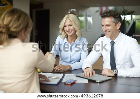 Shot of an investment manager shaking hands with smiling woman while consulting with middle aged couple about financial savings.