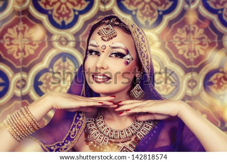Shot of an oriental woman in a traditional costume, smiling, hands under the chin - stock photo