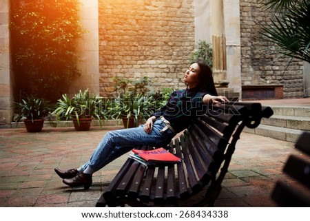 Shot of charming young woman leaning on wooden bench with clothes eyes and enjoying outdoors, beautiful young woman enjoy her leisure time outside, flare sun light, cross process image - stock photo