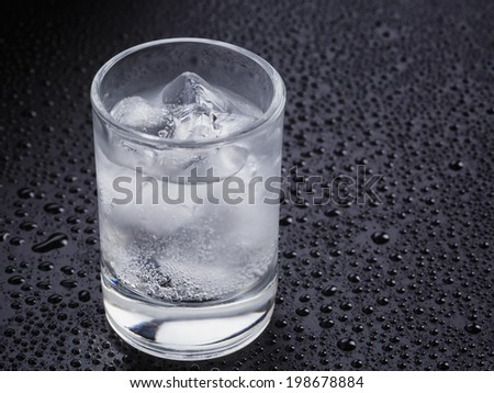 shot of cold sparkling alchoholon table with drops - stock photo