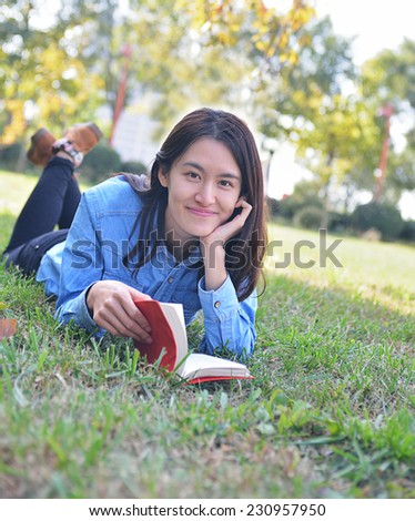 Shot of college student studying on campus lawn - stock photo
