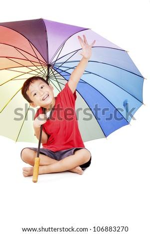 Shot of cute asian boy smiling under multicolored umbrella. shot in studio - stock photo