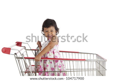 Shot of cute asian girl on the shopping cart shot in studio isolated on white - stock photo