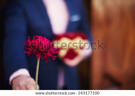 Shot of elegant man giving a red flower while holding Saint Valentine's gift against his chest - stock photo