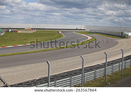 Shot of empty auto racing racetrack turn in summer cloudy day - stock photo