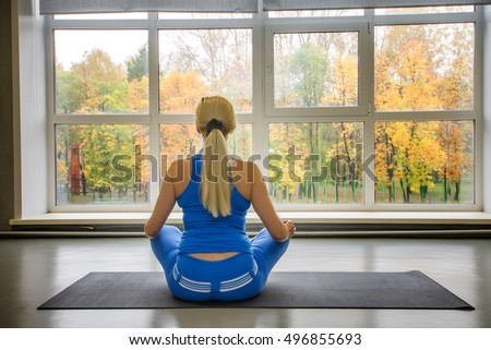 Shot of fitness woman sitting on exercise mat at fitness club.