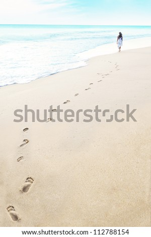 Shot of footprints with woman walks on the tropical beach. Shot in maldives - stock photo