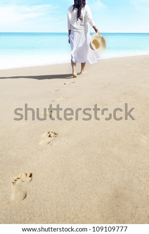 Shot of footprints with woman walks on the tropical beach. shot outdoor