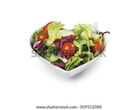 shot of fresh salad in a heart shaped bowl implying healthy living isolated on white with a clipping path and copy space for the designer.  - stock photo