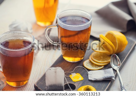 Shot of glass cup of tea with lemon on wood table