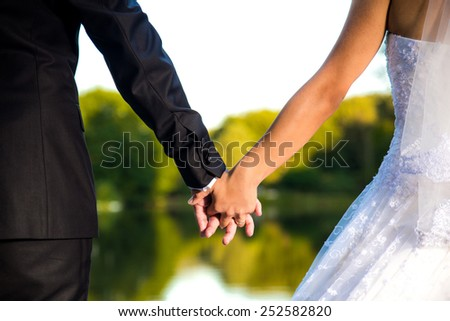 Shot of Groom and bride holding hands from back - stock photo