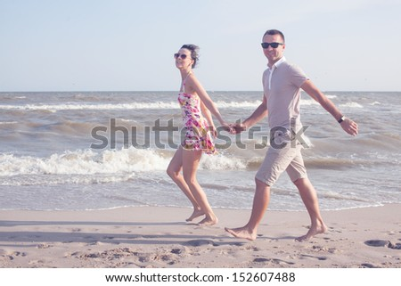 shot of happy smiling couple. Walking on the beach. Holding each other and smiling - stock photo