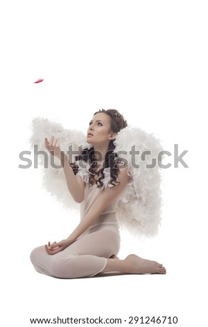 Shot of lovely guardian angel looks at red feather - stock photo