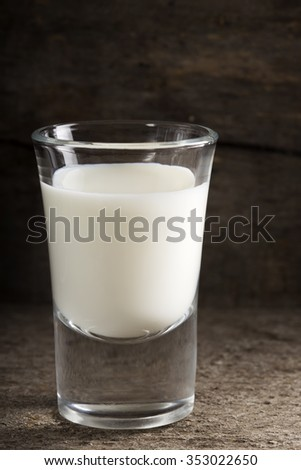 Shot of milk standing on old wooden table - stock photo