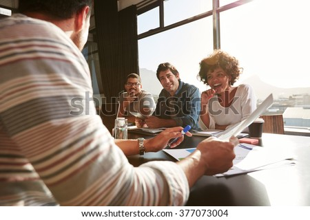 Shot of mixed race young people sitting at a table discussing new and creative business ideas. Smiling african woman sitting with colleagues in a meeting. - stock photo