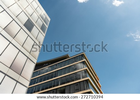 Shot of modern building midday with blue sky - stock photo