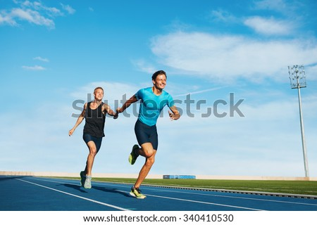 Shot of professional male athletes passing over the baton while running on the track. Athletes practicing relay race on racetrack. - stock photo