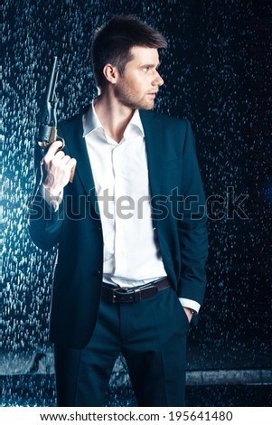 shot of quiet businessman with gun - stock photo