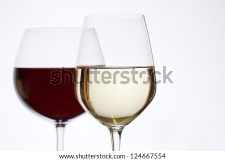 Shot of red and white wine in elegant glasses.