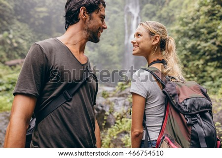 Shot of romantic young couple together on hike. Young man and woman with backpack hiking in nature looking at each other and smiling.