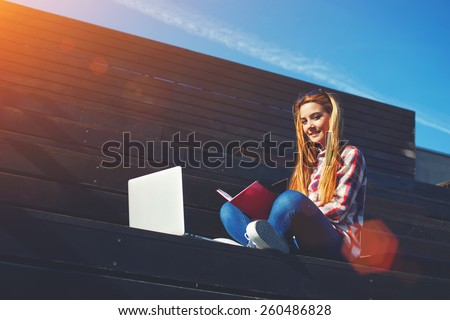Shot of smiling college student studying with book and laptop computer at campus, attractive young woman using laptop sitting on wooden staircase enjoying sunny day outdoors, flare sun light, filter - stock photo