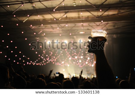Shot of some fans during a life concert of a famous british band. Focus on a happy man with a beer on his hand. - stock photo