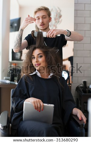 Shot of stylist-barber who does styling comb, brushing a beautiful young model. Beauty Salon- Stylist makes hair beautiful girl with a tablet. a satisfied client in the beauty salon. - stock photo