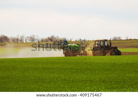 Shot of the employee performing maintenance on the green field.
