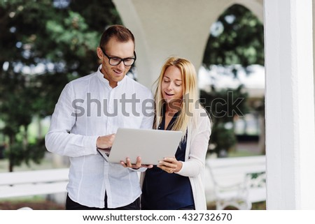 Shot of two coworkers discussing something on a laptop outside. - stock photo