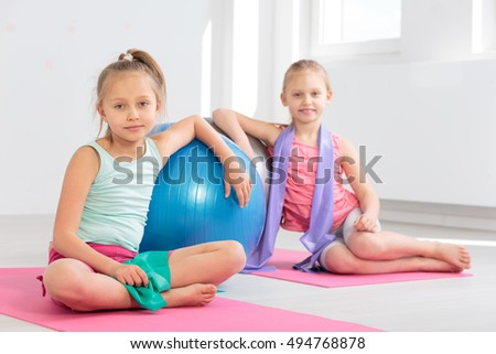 Shot of two girls leaning against balls while resting after their gymnastic classes