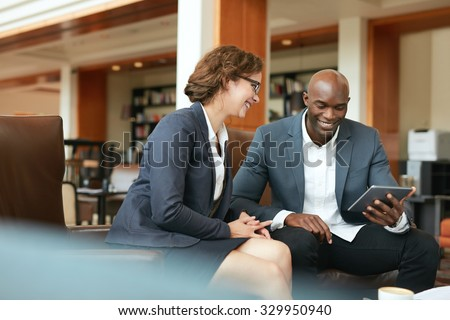 Shot of two people looking at something on a touchscreen computer. Smiling business people using digital tablet while sitting at coffee shop. - stock photo