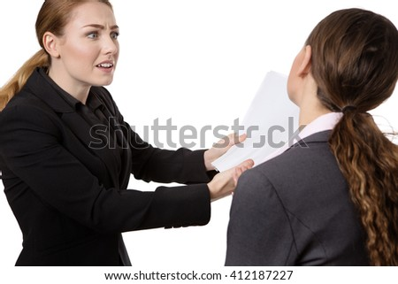 shot of two pretty business women.  One is looking very concerned about the document in her hand.  The other woman is seen from behind.  isolated on white