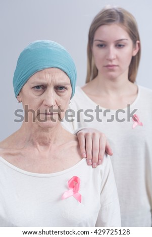 Shot of two women wearing pink ribbons, an international symbol of breast cancer awareness - stock photo
