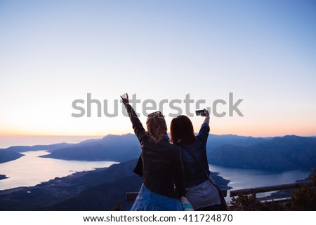 Shot of two young female tourist taking self-portrait pictures in the view from the top of a mountain - stock photo