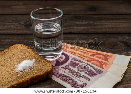 Shot of vodka with money of the Soviet Union and piece of bread with salt on an old wooden table. Close up view, focus on the piece of bread with salt