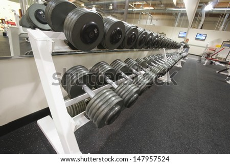 Shot of weight training equipment in a row at the gym - stock photo