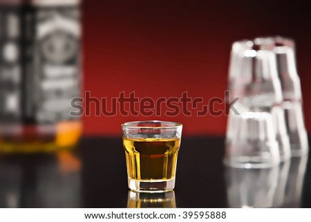 Shot of whiskey on a bar with bottle
