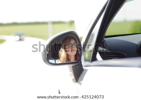 Shot of wing mirror reflection a middle age woman face while sitting in her breakdown car on the road.