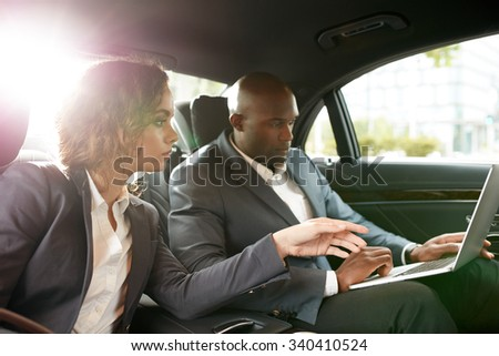 Shot of young business associates travelling to work in the luxury car on the back seat working on laptop. Discuss business strategy while driving to a meeting. - stock photo