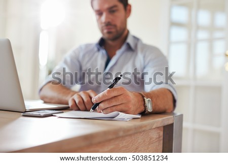 Shot of young businessman sitting at home office with laptop and signing documents. Young man working from home.